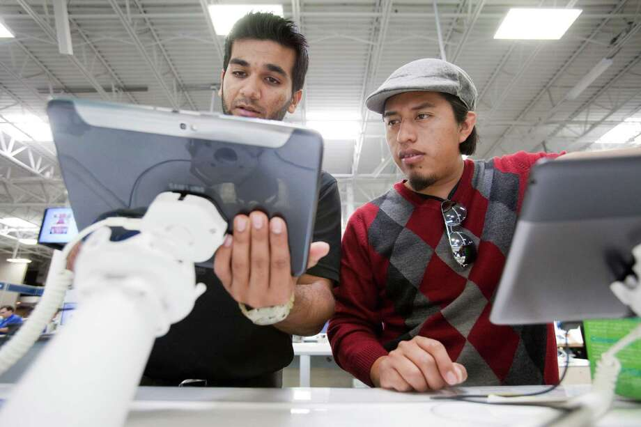 Shahab Shaikh, left, of Best Buy talks with Henry Gonzalez about tablet options at the chain's Bunker Hill location. Photo: Eric Kayne / © Eric Kayne