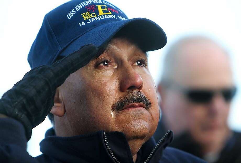 "USS Enterprise alumnus Jimmy Gonzales struggles to hold back tears during a ceremony to honor those who were killed in the Jan. 14, 1969 fire, on the ships flight deck at Naval Station Norfolk, Va. on Friday, Nov. 30, 2012, Gonzales, who lives near Dallas, set foot on The Big E for the first time since he was an 18 year-old Seaman Apprentice who helped care for the wounded and dying. ""I hadn't even made it to Vietnam yet,"" Gonzales remembers, ""and I had already seen more than most.""  Thousands of alumni will visit the ship this weekend during the carrier's inactivation ceremony events at Naval Station Norfolk. Photo: Stephen M. Katz, Associated Press"