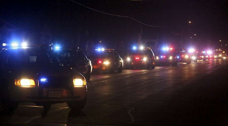 Police and sheriff vehicles followed behind the hearse carrying the body of fallen police officer Tom Decker as they go to Wenners Funeral home in Cold Spring,  Min., Friday  November 30,  2012. Officer Tom Decker, a six-year veteran and father of four, had gone to check on a man's welfare when he was fatally shot after getting out of his squad car near a downtown bar in Cold Springs on Thursday night. Investigators said Friday that several guns were found, and the man who was reported to be suicidal was taken into custody. Photo: Kyndell Harkness, Associated Press