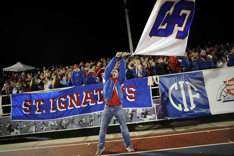 Senior Phil Otto waves a flag in front of the stands on the St. Ignatius side of the field.  St. Ignatius played Bellarmine in the CCS Open Division final at San Jose City College in San Jose, CA Friday November 30th, 2012. Photo: Michael Short, Special To The Chronicle