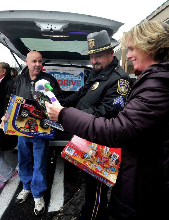 "Richard Rios, left, and Kathleen McLoughlan, right, donate toys to Sgt. Rick Montefusco outside Walmart in Danbury during the ""Stuff a Cruiser"" toy drive Saturday, Dec. 1, 2012. Photo: Michael Duffy"