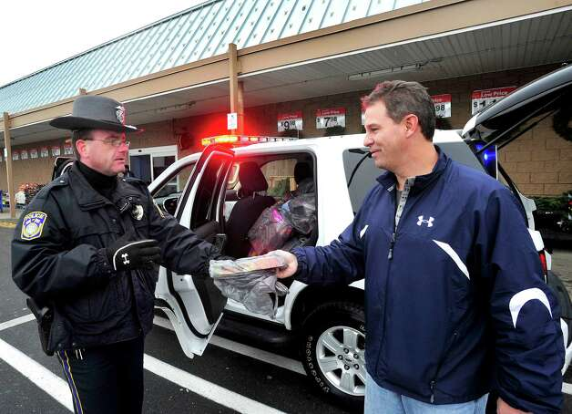 "Officer Shane Dufresne accepts a donation from Kevin Golembeski outside Walmart in Danbury during the ""Stuff a Cruiser"" toy drive Saturday, Dec. 1, 2012. Photo: Michael Duffy"