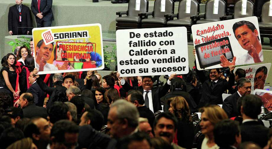"Members of the Revolucion Democratica party hold banners in protest before the arrival of incoming President Enrique Pena Nieto for his inauguration ceremony at the Congress in Mexico City on December 1, 2012. Pena Nieto was sworn in as president of Mexico on Saturday following protests by leftist lawmakers inside the congress and clashes between demonstrators and police outside. The central banner reads ""From a failed state with Calderon to a sold-out state with with his succesor"". AFP PHOTO/Alfredo EstrellaALFREDO ESTRELLA/AFP/Getty Images Photo: ALFREDO ESTRELLA, AFP/Getty Images / ALFREDO ESTRELLA"