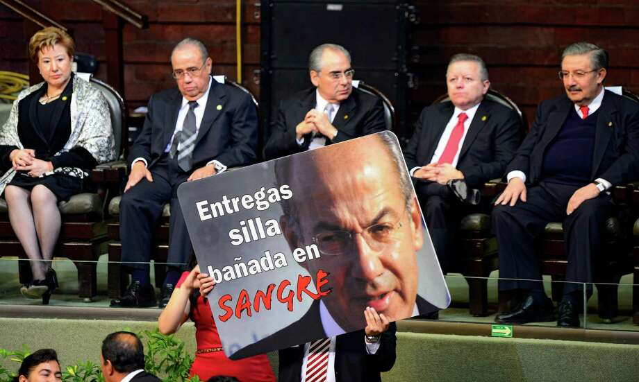 """A member of the Revolucion Democratica party holds a banner portraying outgoing Mexican President Felipe Calderon and reading """"You pass on a chair soaked in blood"""" before the arrvial of incoming President Enrique Pena Nieto for his inauguration ceremony at the Congress in Mexico City on December 1, 2012. Pena Nieto was sworn in as president of Mexico on Saturday following protests by leftist lawmakers inside the congress and clashes between demonstrators and police outside. AFP PHOTO/Alfredo EstrellaALFREDO ESTRELLA/AFP/Getty Images Photo: ALFREDO ESTRELLA, AFP/Getty Images / ALFREDO ESTRELLA"""