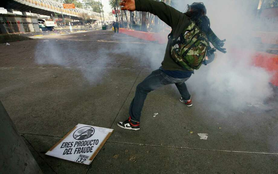 "A demonstrator throws a stone to police during protests against new Mexican President Enrique Pena Nieto's rule, outside the National Congress, in Mexico City, Saturday, Dec. 1, 2012.   Pena Nieto took the oath of office as Mexico's new president on Saturday amid protests inside and outside the congressional chamber where he swore to protect the constitution and laws of the land. At least two protesters were injured, one gravely. The sign on the floor reads in Spanish "" you are a product of fraud "" referred to Pena Nieto.(AP Photo/Marco Ugarte) Photo: Marco Ugarte, Associated Press / AP"