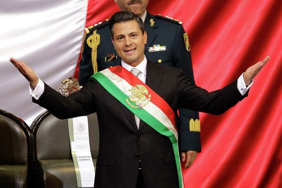 Mexico's incoming President Enrique Pena Nieto spreads out his arms after being sworn in at the inauguration ceremony in National Congress, in Mexico City, Saturday, Dec. 1, 2012. Pena Nieto took the oath of office as Mexico's new president on Saturday, bringing the old ruling party back to power after a 12-year hiatus amid protests inside and outside the congressional chamber where he swore to protect the constitution and laws of the land. (AP Photo/Alexandre Meneghini) Photo: Alexandre Meneghini, Associated Press / AP
