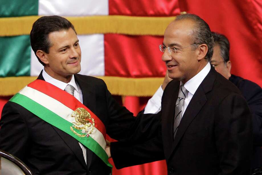 Mexico's incoming President, Enrique Pena Nieto, left, smiles as he stands with outgoing President Felipe Calderon during the inauguration ceremony at the National Congress in Mexico City, Saturday, Dec. 1, 2012.  Pena Nieto took the oath of office as Mexico's new president on Saturday, bringing the old ruling party back to power after a 12-year hiatus amid protests inside and outside the congressional chamber where he swore to protect the constitution and laws of the land. (AP Photo/Alexandre Meneghini) Photo: Alexandre Meneghini, Associated Press / AP