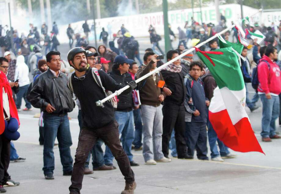 Demonstrators protest outside the Congress in Mexico City during the inauguration of Mexican President Enrique Peña Nieto, on December 1, 2012. Enrique Peña Nieto was sworn in as president of Mexico on Saturday following protests by leftist lawmakers inside the congress and clashes between demonstrators and police outside.  AFP PHOTO/Pedro PardoPedro PARDO/AFP/Getty Images Photo: PEDRO PARDO, AFP/Getty Images / AFP
