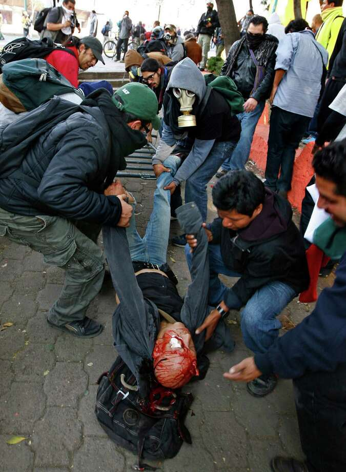 A seriously injured man is carried by demonstrators after he was hit with a tear gas canister shot by riot police during protests against new Mexican President Enrique Pena Nieto's rule, outside the National Congress, in Mexico City, Saturday, Dec. 1, 2012.   Pena Nieto took the oath of office as Mexico's new president on Saturday amid protests inside and outside the congressional chamber where he swore to protect the constitution and laws of the land. At least two protesters were injured, one gravely.(AP Photo/Marco Ugarte) Photo: Marco Ugarte, Associated Press / AP