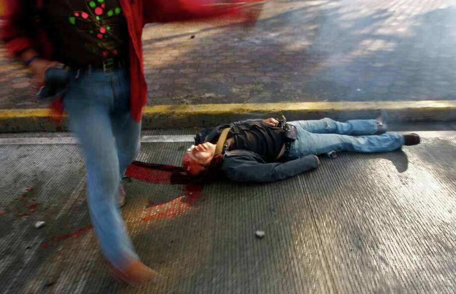 A seriously injured man lies on the ground bleeding from his head after he was hit with a tear gas canister shot by riot police during protests against new Mexican President Enrique Pena Nieto's rule, outside the National Congress, in Mexico City, Saturday, Dec. 1, 2012.   Pena Nieto took the oath of office as Mexico's new president on Saturday amid protests inside and outside the congressional chamber where he swore to protect the constitution and laws of the land. At least two protesters were injured, one gravely.(AP Photo/Marco Ugarte) Photo: Marco Ugarte, Associated Press / AP
