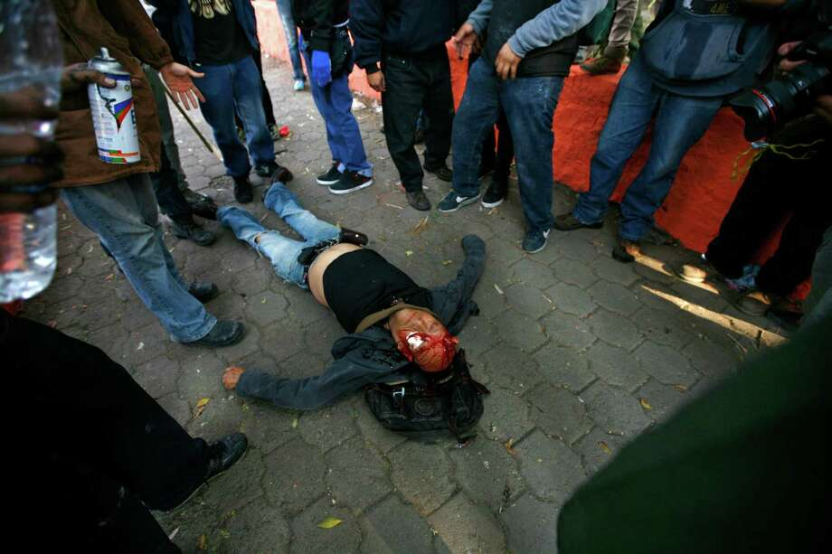 A seriously injured man lies bleeding from his head after he was hit with a tear gas canister shot by riot police during protests against new Mexican President Enrique Pena Nieto's rule, outside the National Congress, in Mexico City, Saturday, Dec. 1, 2012.   Pena Nieto took the oath of office as Mexico's new president on Saturday amid protests inside and outside the congressional chamber where he swore to protect the constitution and laws of the land. At least two protesters were injured, one gravely.(AP Photo/Marco Ugarte) Photo: Marco Ugarte, Associated Press / AP