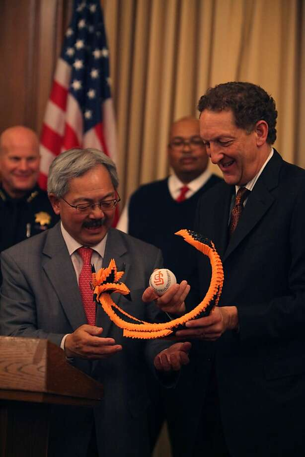 Mayor Ed Lee (l to r) stands with Giants CEO Larry Baer as Baer holds a paper dragon carrying a World Series ball presented to him during a press conference regarding the World Series Championship Parade and Civic Celebration at the Mayor's Office on Tuesday, October 30, 2012 in San Francisco, Calif. Photo: Lea Suzuki, The Chronicle