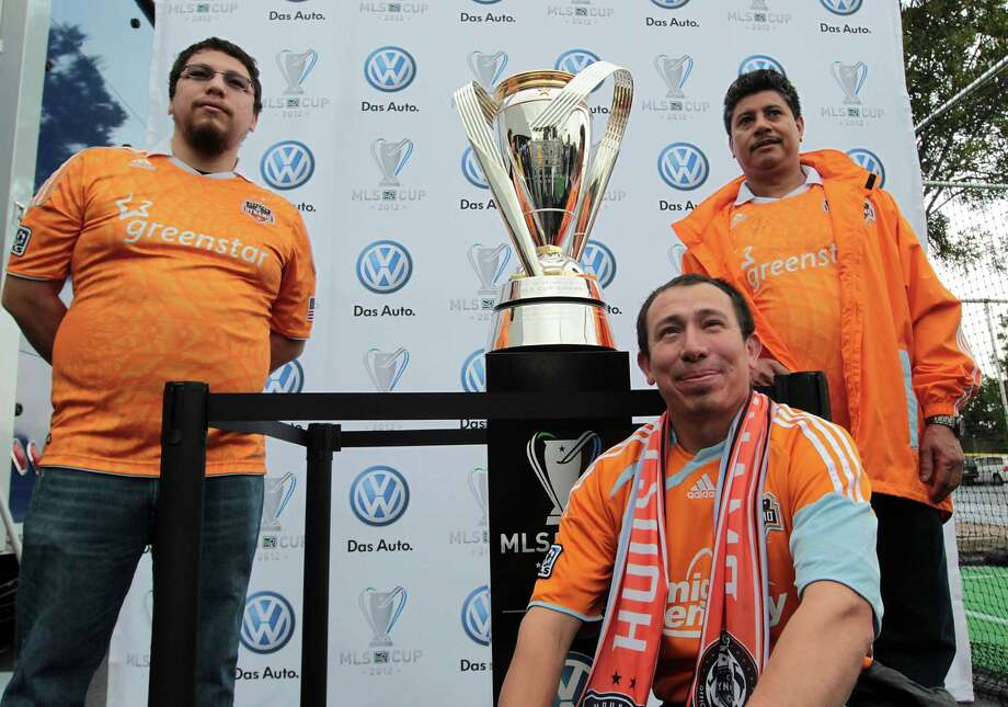 Levy Fuentes left, Rigo Reyes center, and Jose Fuentes take a photograph with Philip F. Anschutz Trophy before the 2012 MLS Cup championship between the Los Angeles Galaxy and the Houston Dynamo at the Home Depot Center Saturday, Dec. 1, 2012, in Los Angeles. Photo: James Nielsen, Chronicle / © Houston Chronicle 2012