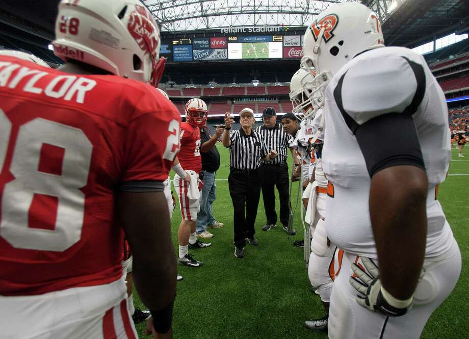 A referee performs the coin toss before a Class 5A Division II playoff game between Katy and La Porte. Photo: Bob Levey, Houston Chronicle / ©2012 Bob Levey