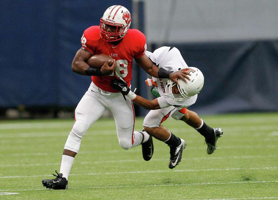 Katy's Adam Taylor stiff arms La Porte's Victor  Holmes as he rushes in the first quarter. Photo: Bob Levey, Houston Chronicle / ©2012 Bob Levey