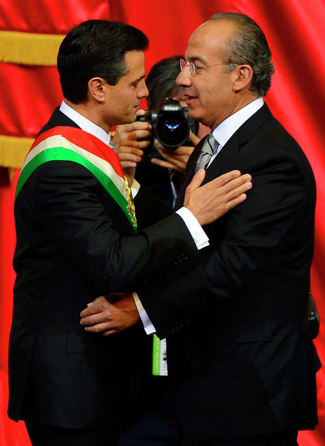 Mexican new President Enrique Pena Nieto is congratulated by outgoing President Felipe Calderon (R) during his inauguration at the Congress in Mexico City, on December 1, 2012. Enrique Pena Nieto was sworn in as president of Mexico on Saturday following protests by leftist lawmakers inside the congress and clashes between demonstrators and police outside.  AFP PHOTO/ALFREDO ESTRELLAALFREDO ESTRELLA/AFP/Getty Images Photo: ALFREDO ESTRELLA, AFP/Getty Images / ALFREDO ESTRELLA