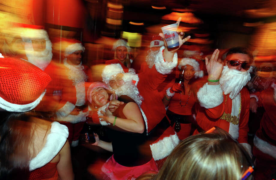 Locals dressed as Santas dance to music during Bridgeport Wingding and Black Rock Life's 1st Annual Rock'n the Ave SantaCon 2012 pubcrawl at The Creek in Bridgeport, Conn. on Saturday December 1, 2012. Participants dressed up as Santa or other holiday characters and made their way to six other bars along Fairfield Avenue taking part in the event. Photo: Christian Abraham / Connecticut Post