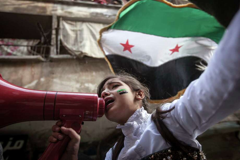 In this Friday, Nov. 30, 2012 photo, a Syrian girl chants slogans during a demonstration after Friday prayers in the Bustan Al-Qasr district of Aleppo, Syria. After months of fighting, thousands of residents have returned to the city as they attempt to return to their daily lives while heavy fighting is still taking place along the front lines in the city. Public demonstrations have unfolded after several weeks of silence as residents demand an end to the violence in Aleppo. (AP Photo/Narciso Contreras) Photo: Narciso Contreras, Associated Press / AP