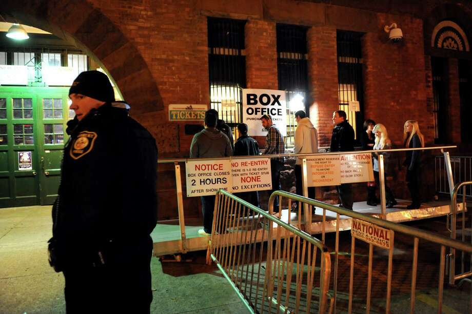 Masquerave participants buy tickets as an Albany Police Officer monitors the scene on Friday, Nov. 30, 2012, at the Washington Armory in Albany, N.Y. (Cindy Schultz / Times Union) Photo: Cindy Schultz / 00020313A