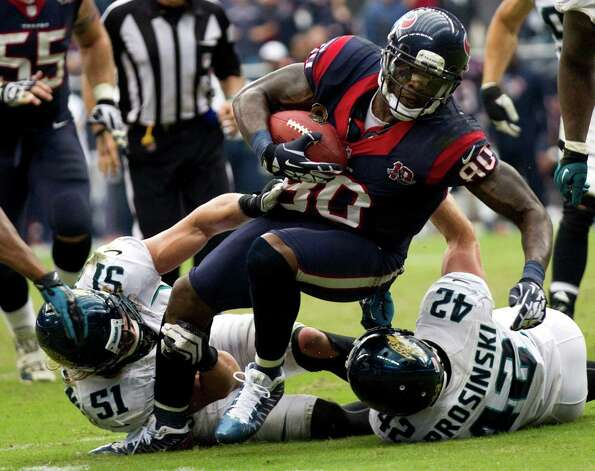 Houston Texans wide receiver Andre Johnson (80) is brought down by Jacksonville Jaguars middle linebacker Paul Posluszny (51) and Jaguars free safety Chris Prosinski (42) on a 14-yard reception near the goal line during the fourth quarter at Reliant Stadium on Sunday, Nov. 18, 2012, in Houston. The Texans beat the Jaguars 43-37. Photo: Brett Coomer, Houston Chronicle / © 2012  Houston Chronicle