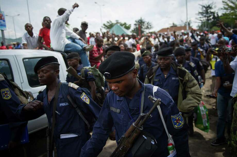 A crowd cheers as Congolese National Police-officers march into the central bank in the city of Goma in the east of the Democratic Republic of the Congo on December 1, 2012. Hundreds of Congolese M23 rebels began a withdrawal on December 1 from Goma as promised under a regionally brokered deal, after a 12-day occupation of the city. Around 300 rebels, army mutineers who seized Goma last week in a lightning advance, were seen by an AFP reporter driving in a convoy of looted trucks north out the main town in Democratic Republic of Congo's mineral-rich east. AFP PHOTO/PHIL MOOREPHIL MOORE/AFP/Getty Images Photo: PHIL MOORE, AFP/Getty Images / © Phil Moore