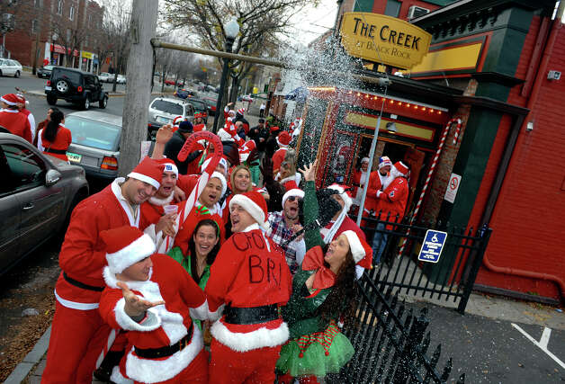 Locals dressed as Santas hang out in front of The Creek during Bridgeport Wingding and Black Rock Life's 1st Annual Rock'n the Ave SantaCon 2012 pubcrawl on Fairfield Avenue in Bridgeport, Conn. on Saturday December 1, 2012. Participants dressed up as Santa or other holiday characters and made their way to six other bars along Fairfield Avenue taking part in the event. Photo: Christian Abraham / Connecticut Post