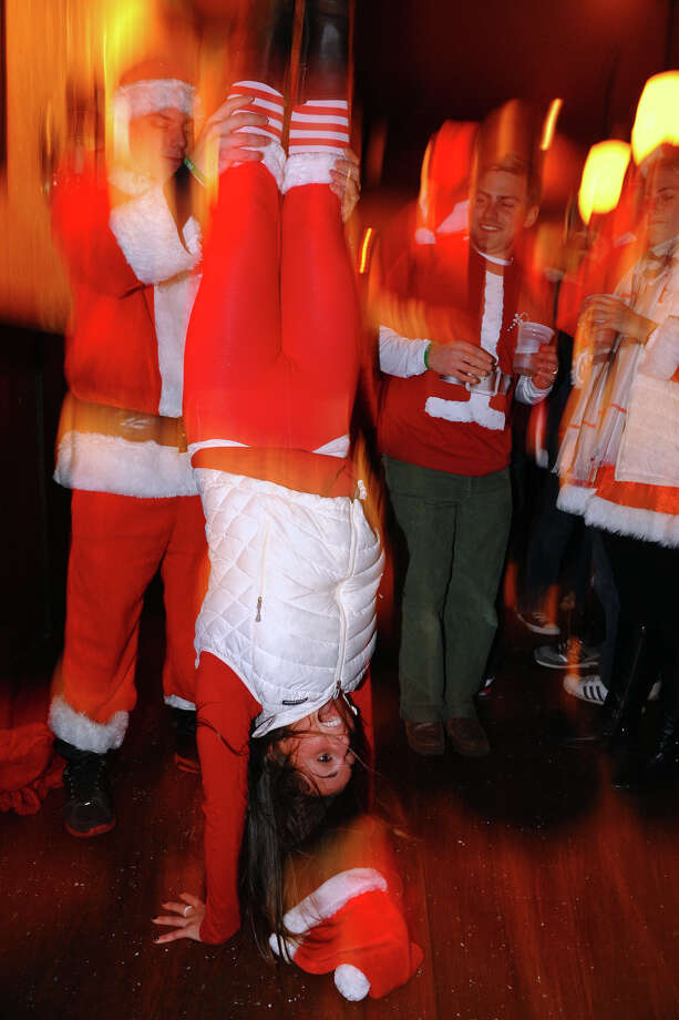 Locals dressed as Santas take part in Bridgeport Wingding and Black Rock Life's 1st Annual Rock'n the Ave SantaCon 2012 pubcrawl at The Creek in Bridgeport, Conn. on Saturday December 1, 2012. Participants dressed up as Santa or other holiday characters and made their way to six other bars along Fairfield Avenue taking part in the event. Photo: Christian Abraham / Connecticut Post