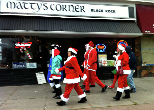 Locals dressed as Santas make their way past Matty's Corner along Fairfield Avenue during Bridgeport Wingding and Black Rock Life's 1st Annual Rock'n the Ave SantaCon 2012 in Bridgeport, Conn. on Saturday December 1, 2012. Participants dressed up as Santa or other holiday characters and made their way to six other bars along Fairfield Avenue taking part in the event. Photo: Christian Abraham / Connecticut Post