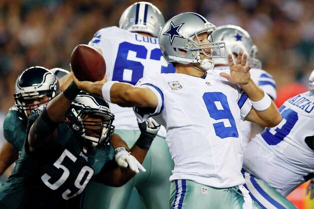 Dallas Cowboys quarterback Tony Romo, right, passes under pressure from Philadelphia Eagles middle linebacker DeMeco Ryans in the first half of an NFL football game, Sunday, Nov. 11, 2012, in Philadelphia. (AP Photo/Julio Cortez) Photo: Julio Cortez, Associated Press / AP