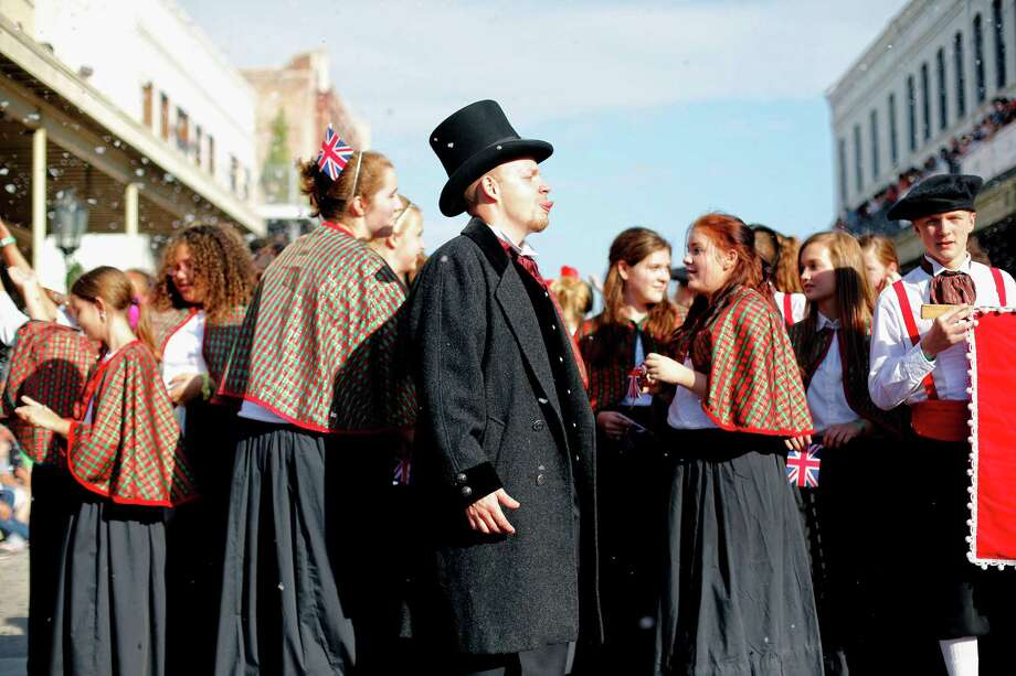 Members of the Katy junior high choir stop to revel in the falling faux snow, Saturday, December 1, 2012 during the annual Dickens on The Strand celebration in Galveston, Texas. Photo: TODD SPOTH, For The Chronicle / Todd Spoth
