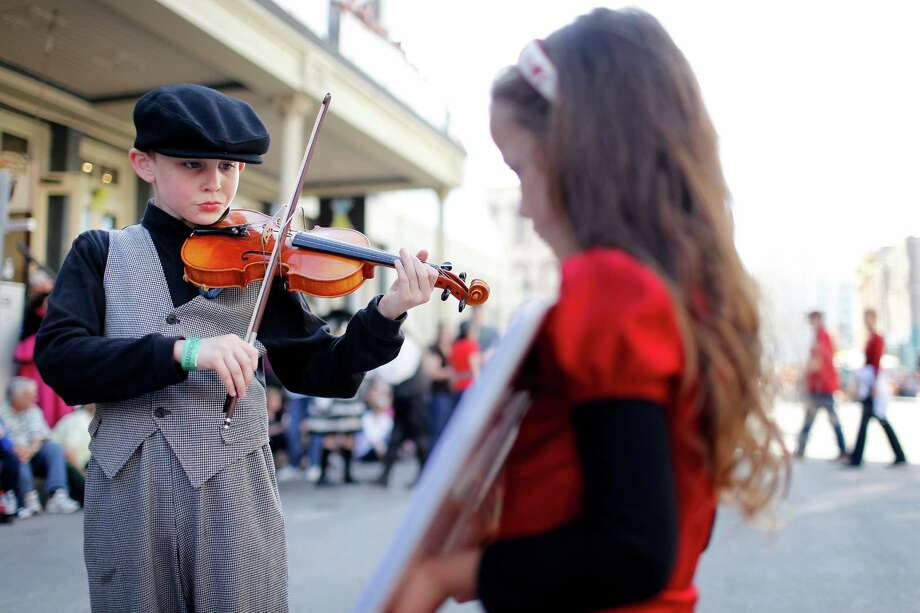Travis Gibson, 9, left, plays the violin as sister, Mary Cathryn, 6, right, displays sheet music, Saturday, December 1, 2012 during the annual Dickens on The Strand celebration in Galveston, Texas. Photo: TODD SPOTH, For The Chronicle / Todd Spoth