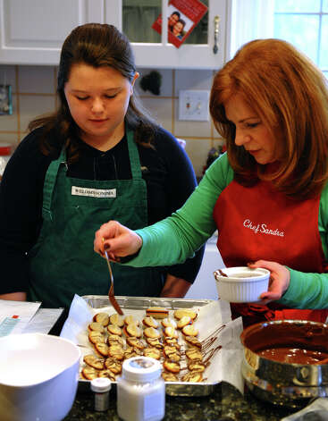 "Sandra Lee, right, shows neighbor Claire McCann, 10, how to makes cookies at her home in Easton, Conn. on Saturday December 1, 2012. Sandra and her longtime freind Cindy Slipko, known as ""The Cookie Ladies,"" have been baking together every December 1st for 30 years. Together with friends, they bake over 7,000 cookies to give out to anyone who needs a special gift during the holidays, such as to the troops, local hospitals and orphanages to name a few. Photo: Christian Abraham / Connecticut Post"