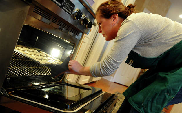 "Neighbor Carolyn McCann checks on a batch of cookies at Sandra Lee's home in Easton, Conn. on Saturday December 1, 2012. Sandra and her longtime freind Cindy Slipko, known as ""The Cookie Ladies,"" have been baking together every December 1st for 30 years. Together with friends, they bake over 7,000 cookies to give out to anyone who needs a special gift during the holidays, such as to the troops, local hospitals and orphanages to name a few. Photo: Christian Abraham / Connecticut Post"