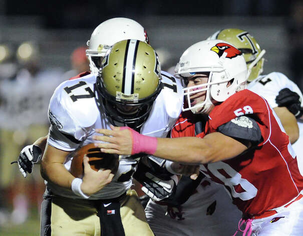 At left, Trumbull quarterback Nick Roberts # 17 gets sacked by Alex McGee # 58 of Greenwich during the boys high school football game between Greenwich High School and Trumbull High School at Greenwich, Friday afternoon, Oct. 5, 2012. Photo: Bob Luckey / Greenwich Time