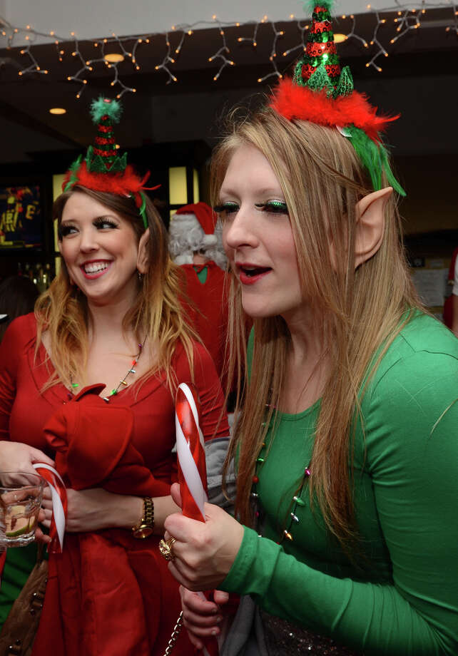 Jessica Alabama, of Carmel, NY, dons a green elf costume with friend, Corrine Seldon, also of Carmel, NY, while at Butterfield8 on Bedford Street in Stamford during the annual Stamford SantaCon pub crawl on Saturday, Dec. 1, 2012. Photo: Amy Mortensen / Connecticut Post Freelance
