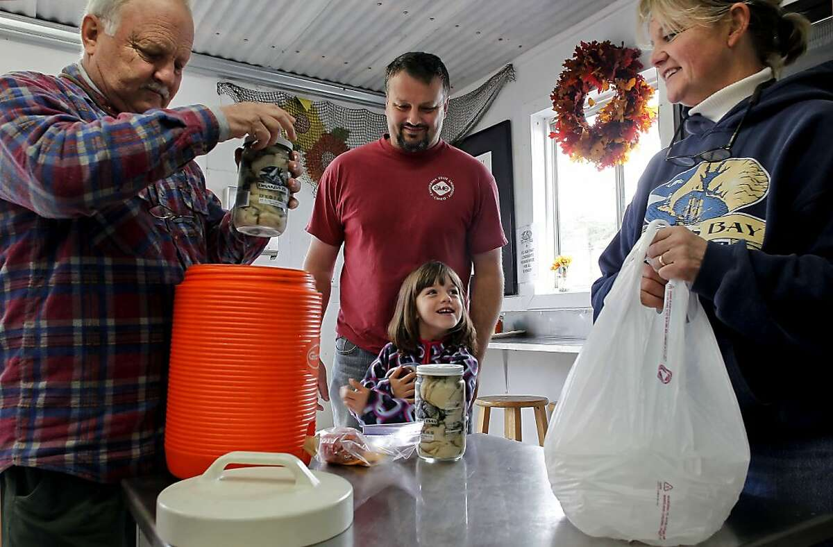 Vance Hamilton, (left) along with his son Chad and grandduaghter Sarah, 5 made the trip from Fremont to buy oysters from farm manager Ginny Lunny-Cummings, in Point Reyes, Calif. on Saturday Dec. 1, 2012. They have been coming to the oyster farm since 1972. The Drakes Bay Oyster Company received notice that U.S. Secretary of the Interior Salazar will not renew their lease and now have 90 days of harvesting and selling their stockpile of oysters before having to vacant the historic Drakes Bay location.