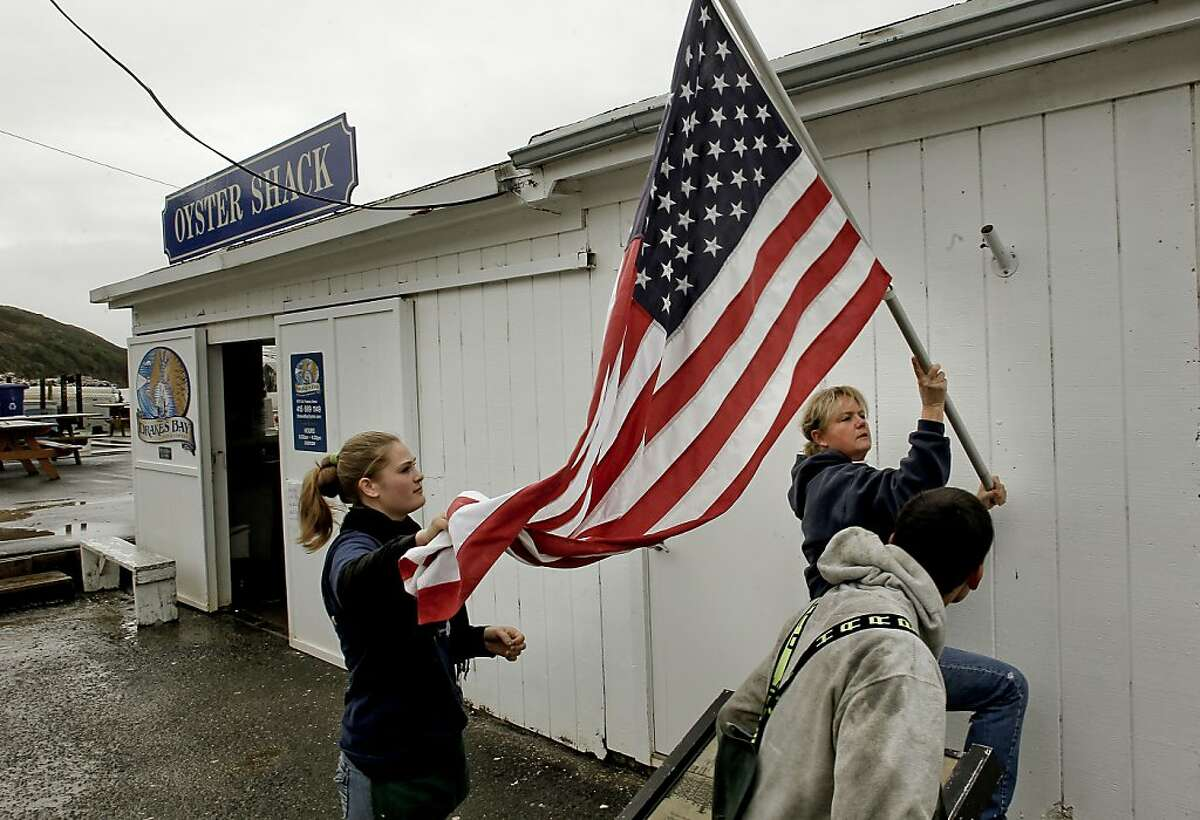 With a break in the rain, farm manager Ginny Lunny-Cummings gets help from her niece Brigid Lunny and nephew Sean Lunny re-hanging their U.S. flag outside their retail shop in Point Reyes, Calif. on Saturday Dec. 1, 2012. The Drakes Bay Oyster Company received notice that U.S. Secretary of the Interior Salazar will not renew their lease and they now have 90 days of harvesting and selling their stockpile of oysters before having to vacate the historic Drakes Bay location.