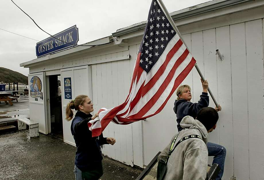 With a break in the rain, farm manager Ginny Lunny-Cummings gets help from her niece Brigid Lunny and nephew Sean Lunny re-hanging their U.S. flag outside their retail shop in Point Reyes, Calif.  on Saturday Dec. 1, 2012. The Drakes Bay Oyster Company received notice that U.S. Secretary of the Interior Salazar will not renew their lease and they now have 90 days of harvesting and selling their stockpile of oysters before having to vacate the historic Drakes Bay location. Photo: Michael Macor, The Chronicle