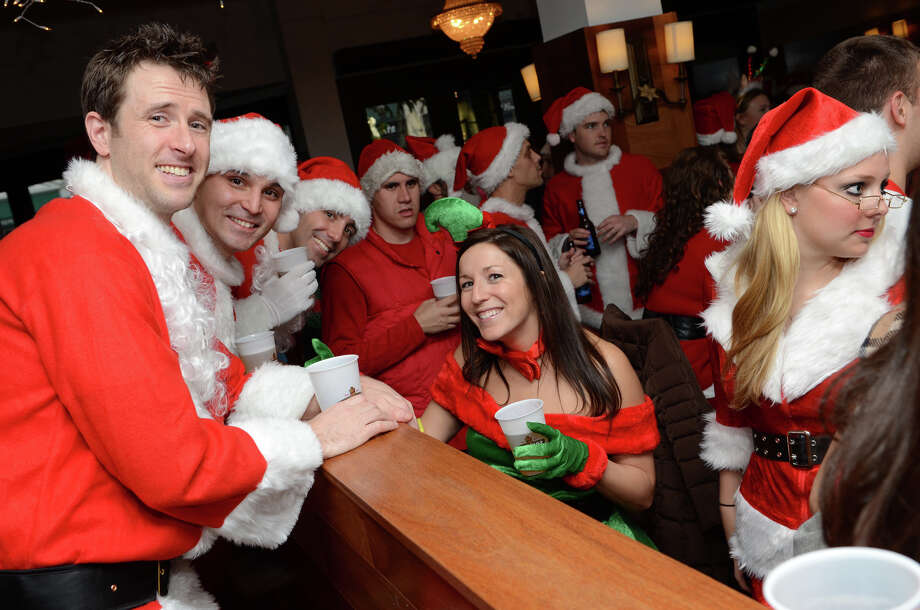 David Busch, of Stamford, Jason Chung, of New Rochelle, NY; Scott McCormack, of Branford, and Jessica Arrien, of Norwalk, pose for a photograph at Butterfield8 on Bedford Street in Stamford during the annual Stamford SantaCon pub crawl on Saturday, Dec. 1, 2012. Photo: Amy Mortensen / Connecticut Post Freelance