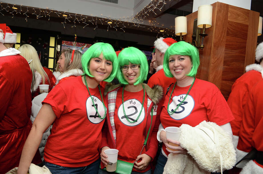 Stamford residents Christin Mone, Irene Serrano and Kristen Frechette, dressed as Ho 1, Ho 2, and Ho 3, pose for a photograph at Butterfield8 on Bedford Street in Stamford during the annual Stamford SantaCon pub crawl on Saturday, Dec. 1, 2012. Photo: Amy Mortensen / Connecticut Post Freelance