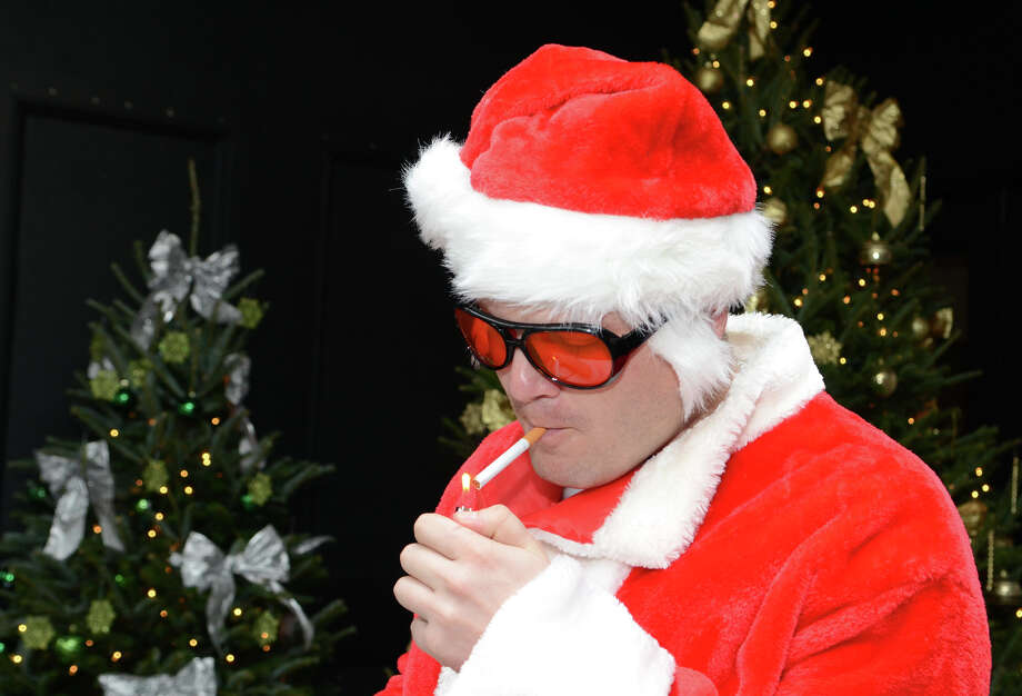 Aram Grigorian, of Stamford, lights a cigarette outside of Butterfield8 on Bedford Street in Stamford during the annual Stamford SantaCon pub crawl on Saturday, Dec. 1, 2012. Photo: Amy Mortensen / Connecticut Post Freelance