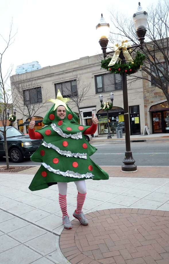 Anthony Giuliano, of West Chester, gives a thumbs up as he strolls down Bedford Street dressed as a Christmas tree before stopping into Tigin's in Stamford during the annual Stamford SantaCon pub crawl on Saturday, Dec. 1, 2012. Photo: Amy Mortensen / Connecticut Post Freelance