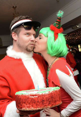 Stu Tackett, of Stamford, receives a birthday kiss from his wife, Michelle, at Butterfield8 on Bedford Street in Stamford during the annual Stamford SantaCon pub crawl on Saturday, Dec. 1, 2012. Photo: Amy Mortensen / Connecticut Post Freelance