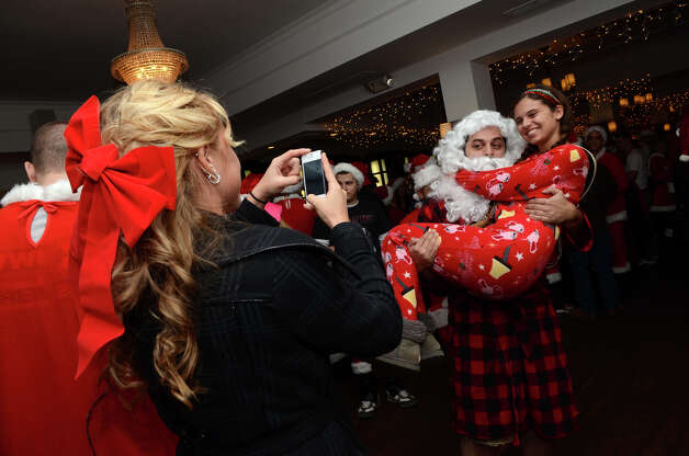 Alex Lane, of Stamford, snaps a photo of Mike Mansury as he carries Erica Farmer while at Butterfield8 on Bedford Street in Stamford during the annual Stamford SantaCon pub crawl on Saturday, Dec. 1, 2012. Photo: Amy Mortensen / Connecticut Post Freelance