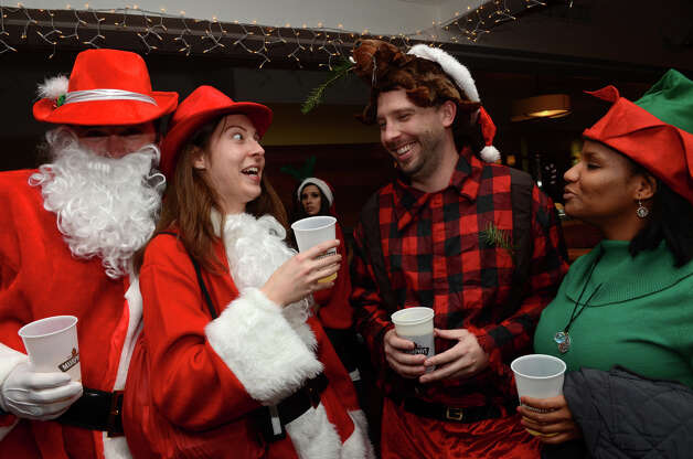 Amy Nazimiec, of Stamford, looks startled as she is greeted by Eric Fearn, of Monroe, Maine, wearing a beaver hat, at Butterfield8 on Bedford Street in Stamford during the annual Stamford SantaCon pub crawl on Saturday, Dec. 1, 2012. With Nazimiec are Tim Vale, far left, and Martha Jiminez, far right. Photo: Amy Mortensen / Connecticut Post Freelance