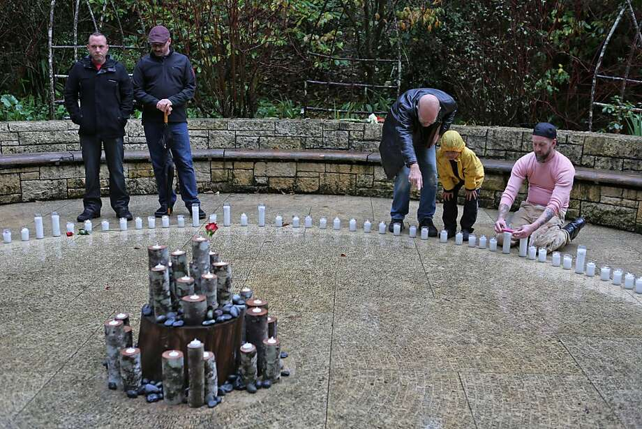 "Steven Dibner (third from right) and son Pablo Dibner search for the etched name of the late Wayne Parrish, a friend and colleague in the San Francisco Symphony, at the ""Circle of Friends"" in the AIDS Memorial Grove.  Friends and family came to find names of supporters and those who have passed away at the ""Circle of Friends"" at the AIDS Memorial Grove in Golden Gate Park, San Francisco, Calif. Saturday marked the 19th annual world AIDS day remembrance, with a national AIDS memorial service at the Grove designed to remember the dead and raise awareness for the living. Photo: Rashad Sisemore, The Chronicle"