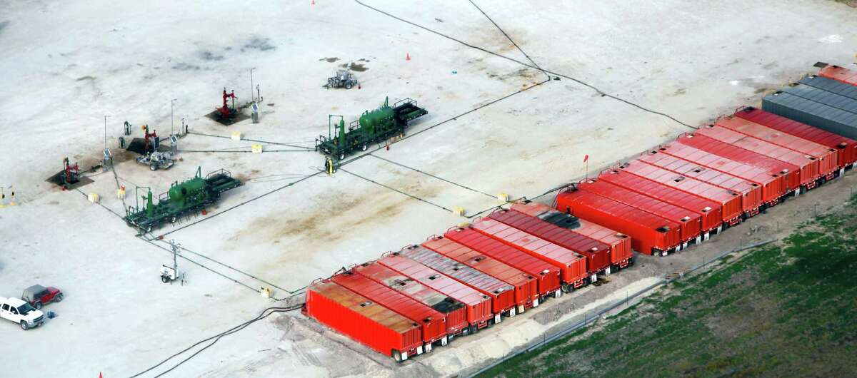 """Three well heads, upper left, in Eagle Ford shale oil play are seen in this Friday Nov. 23, 2012 aerial photo near Kenedy. Red so-called """"frac tanks"""" are positioned at the right edge of the pad site. The containers can each hold 500 barrels of fluid which can be material being prepared to go down the well or material that has come out of the well."""