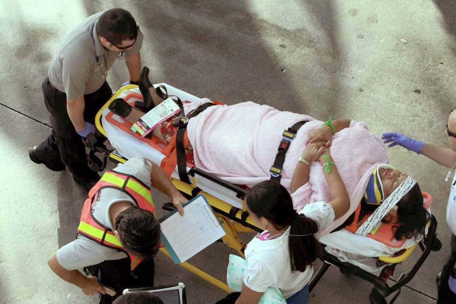 Emergency personnel attend to injured passengers after a bus accident at Miami International Airport on Saturday, Dec. 1, 2012 in Miami. Officials say a bus has hit an overpass, killing at least one person and injuring more than two-dozen people on board. Airport spokesman Greg Chin says the large, white bus hit the overpass going into the airport's arrivals section on Saturday morning. The bus was going about 20 mph when it clipped the roof entrance. Photo: Roberto Koltun, Associated Press / El Nuevo Herald