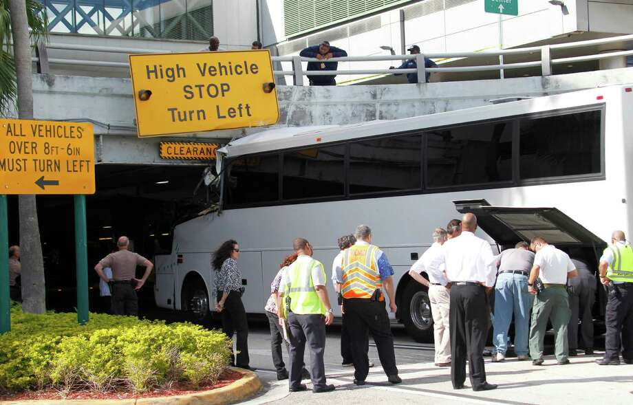 Workers and law enforcement officers prepare to remove a bus after it hit a concrete overpass at Miami International Airport in Miami on Saturday, Dec. 1, 2012. The vehicle was too tall for the 8-foot-6-inch entrance to the arrivals area, and buses are supposed to go through the departures area which has a higher ceiling, according to an airport spokesperson. Photo: Wilfredo Lee, Associated Press / AP