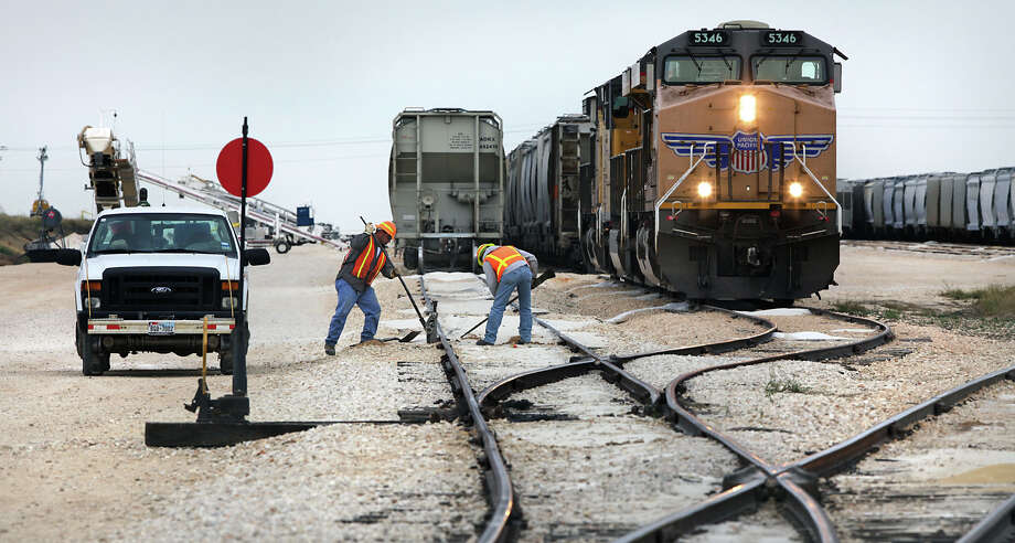 Rail line workers Jeremy Leal, left, and Gilbert Esquivel, both employees of Texas Gonzales and Northern Railway, prepare a railroad line to install a derail.  Operations at the Texas Gonzales and Northern Railway, just outside of Gonzales, Texas have taken off due to the increased business from the Eagle Ford.  Tuesday, Nov. 13, 2012. Photo: Bob Owen, San Antonio Express-News / © 2012 San Antonio Express-News